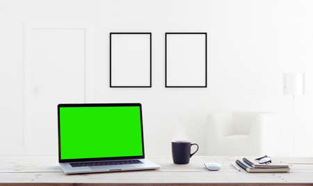 laptop computer showing green screen in home interior background