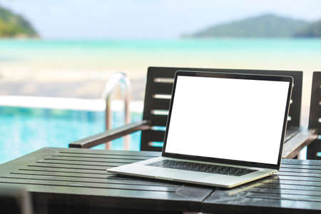 laptop computer showing blank screen on table beauty beach background