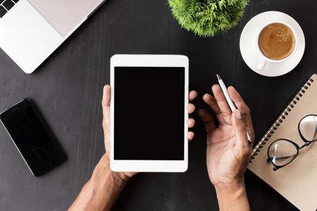 Hand showing digital tablet blank screen on work desk Stok Fotoğraf - 83466162