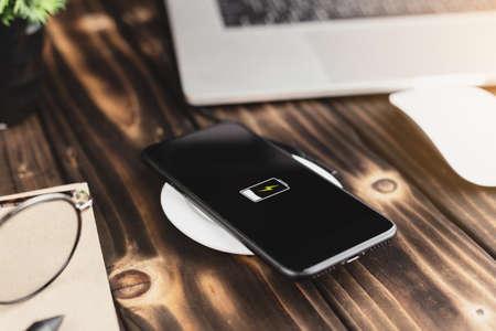 Chargement du téléphone en gros plan sur le chargeur sans fil Banque d'images