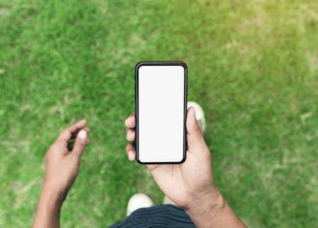 man holding phone showing blank screen walking on lawn 免版税图像