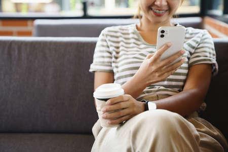 woman feeling happy using phone in coffee shop