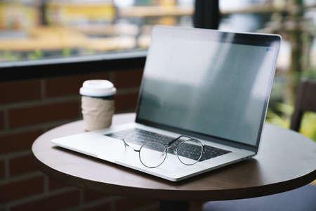 eyeglasess on laptop computer in coffee shop 免版税图像
