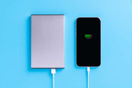phone charging with external power supply on blue background