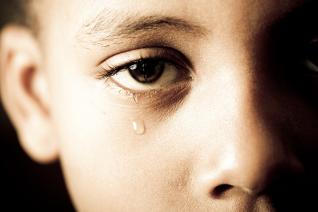 sad eyes: close-up of a boy shedding a tear Stock Photo