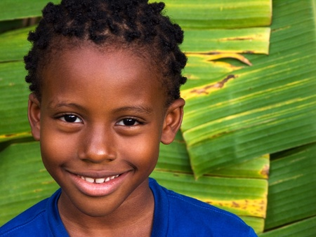 smiling boy with giant banana leaves