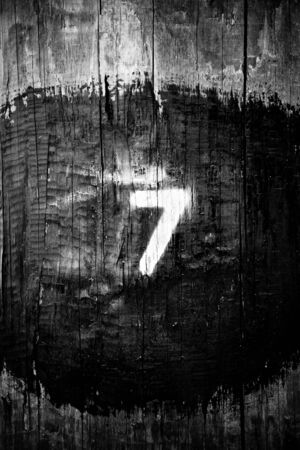seven is large on a wooden post in black and white Stock Photo - 18875596