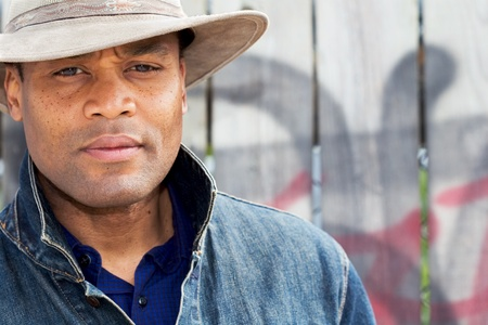 a man in a cowboy hat stands in front of a wooden fence