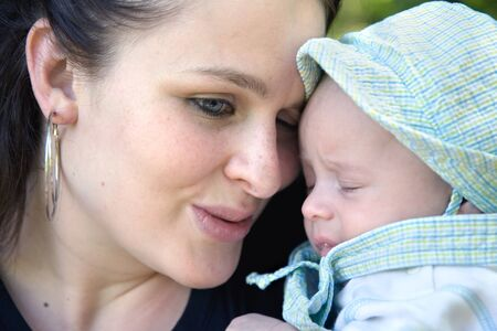 mother and son share a tender moment - focus on woman, baby spitting up photo