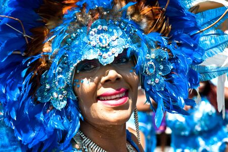 revellers: Trinidad, West Indies - February 5, 2008 - Smiling female masquerader with headdress taking part in Carnival Tuesday celebrations on February 5, 2008 in Port Of Spain, Trinidad W I