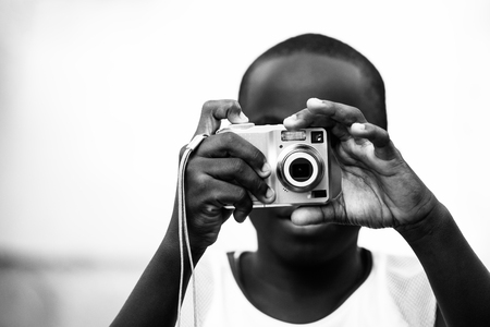 boy taking a photograph with a point and shoot camera Stock Photo