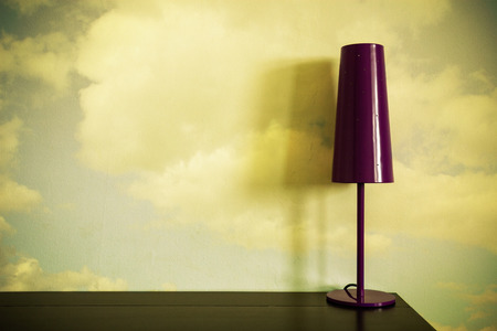 lamp on a desk with clouds on a wall