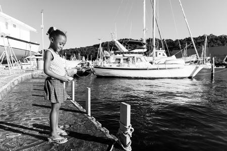 barrettes: bambina in possesso di pietra con le barche in mare Archivio Fotografico