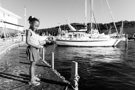 little girl holding stone with boats in the ocean