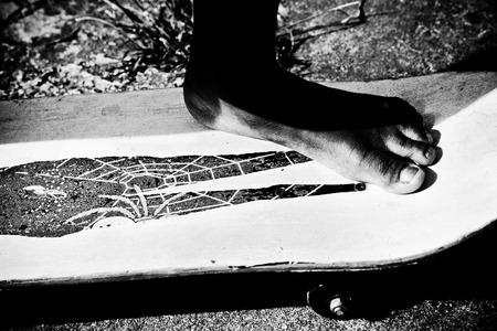 boy barefoot on a skateboard Stock Photo