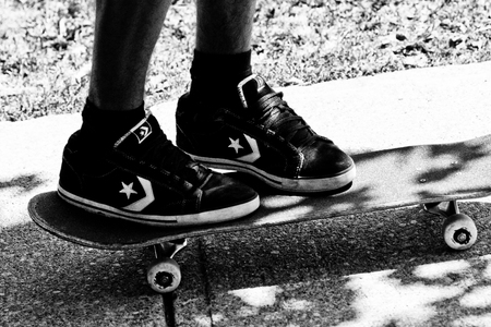 teen wearing converse skate shoes stands on a skateboard Editorial