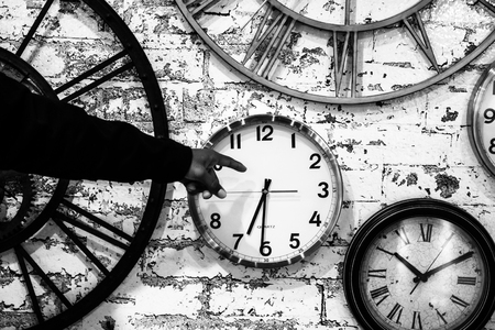 hand points to clocks on a wall