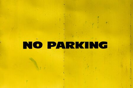 metal gate: no parking sign on a yellow metal gate Stock Photo