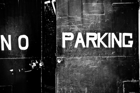 no parking sign on metal gate