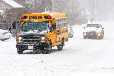 school bus on street in winter during a snowstorm