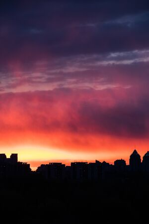 colorful fiery sky at sundown with cirrus clouds above the city skyline