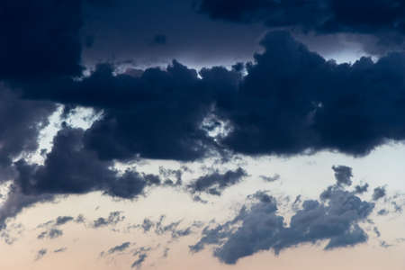 chunky, smoky cumulus clouds in a contrasty sky at sundown