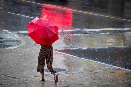 Toronto, Canada - July 24, 2018: woman with a red umbrella on an evening walk downtown, in heavy rain Redakční