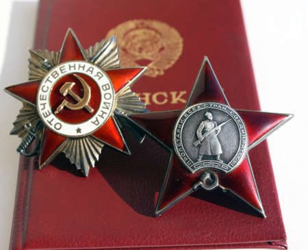 Awards of the USSR. Order Great Patriotic War and Red Star with background of veteran and id soldiers books Editorial