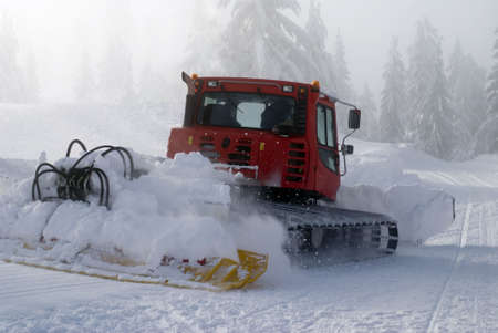 A snowplow prepares a run at a ski resort.