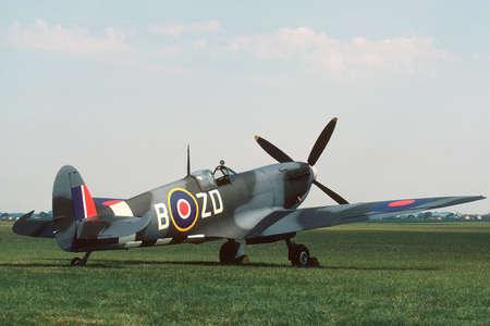 British mark IX Spitfire parked beside a grass runway.