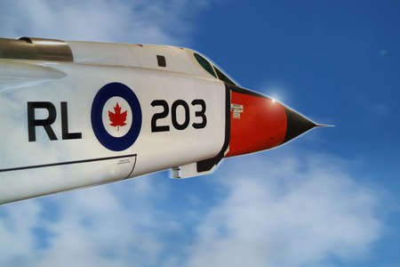 A white Canadian jet interceptor glints in the sun as it breaks out of the clouds, at the speed of sound, and into a clear blue sky.