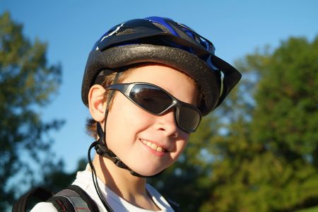 A nine year old boy wearing sunglasses, a bike helmet and a backpack stands in a sunny park with trees and blue sky in the background.