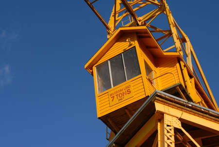 An old yellow freight crane stands against a bright blue sky. Stock Photo