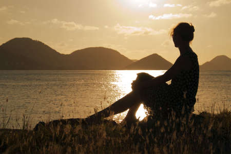 A woman watching the sunset in the Caribbean. Archivio Fotografico