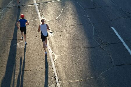 A pair of marathon runners head towards the rising sun during the opening stages of a race. Stock Photo