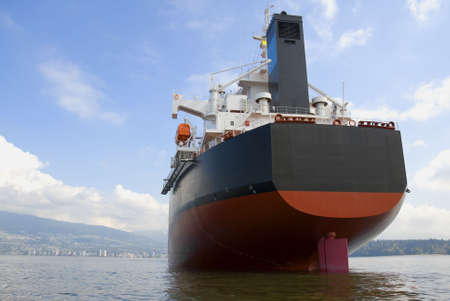 The stern and funnel of an empty freighter anchored off the west coast of North America.