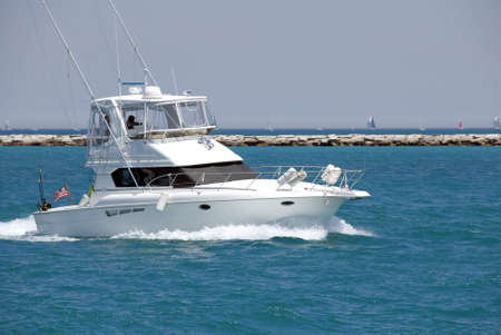 A white sport fishing boat, flying the US Yacht Ensign, heads towards the open sea.