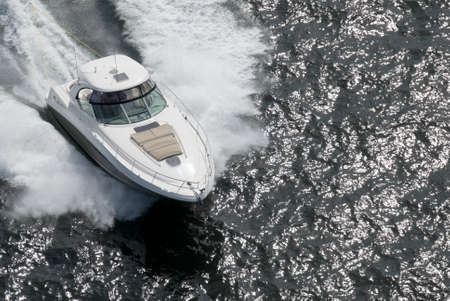 A white and tan speedboat shot from above while travelling fast. Imagens