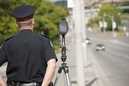 A North American policeman waits to catch speeding drivers with a radar gun. (Shot with minimum depth of field. Focus is on the police officer and radar gun.) Imagens - 2378810