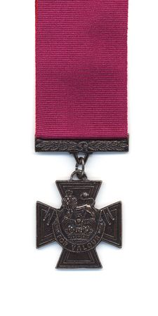 A British Victoria Cross with a crimson ribbon. Medals issued to the Royal Navy prior to 1918 were suspended from a blue ribbon. With the creation of the Royal Air Force the crimson ribbon became standard.