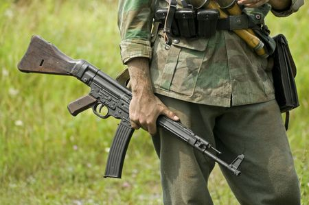A world war two German soldier holding an MP43 submachine gun. Shot with minimum depth of field. Focus is on the hand and gun.