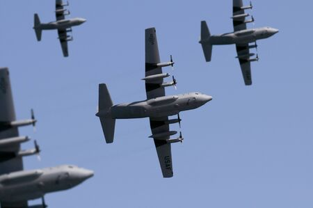 A fleet of USAF Lockheed C-130 Hercules transport planes flying overhead. (Shot with minimum depth of field. Focus is on the centre aircraft.