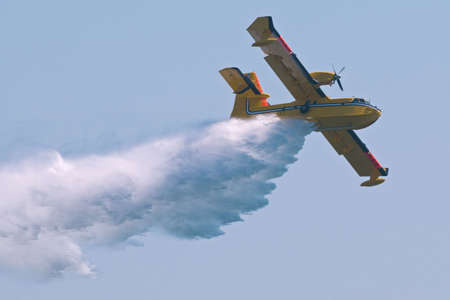A twin-engined  bomber dumping its load on a forest fire.