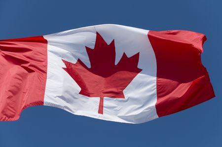 The Canadian flag flying against a bright blue sky. Standard-Bild