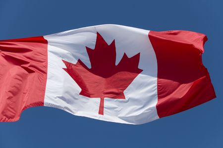 The Canadian flag flying against a bright blue sky. Imagens