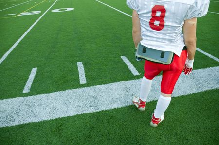 A North American football player standing on the sideline. Imagens