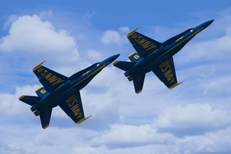 Two F-A18 Hornets from the US Navy Blue Angels Flight Demonstration Squadron flying in formation against a partly cloudy sky.
