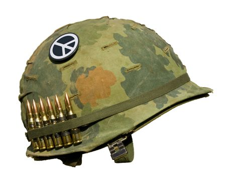 A US military helmet with an M1 Mitchell pattern camouflage cover from the Vietnam war, with six rounds of 7.62mm ammunition and a peace symbol button. Imagens