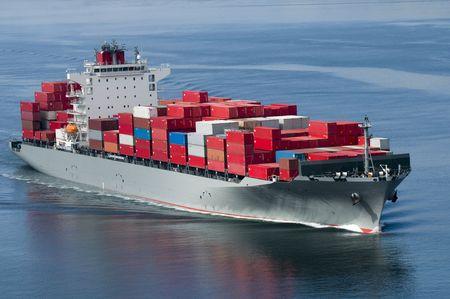 Un barco de contenedores que llegan a puerto en un día muy tranquilo. Foto de archivo