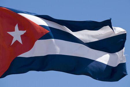 The Cuban flag flying against a bright blue sky. Banco de Imagens